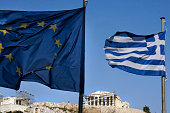 Greek and EU flag flies in front of the ancient Parthenon temple atop the Acropolis hill on January 21 2015 in Athens Greece According to the latest...