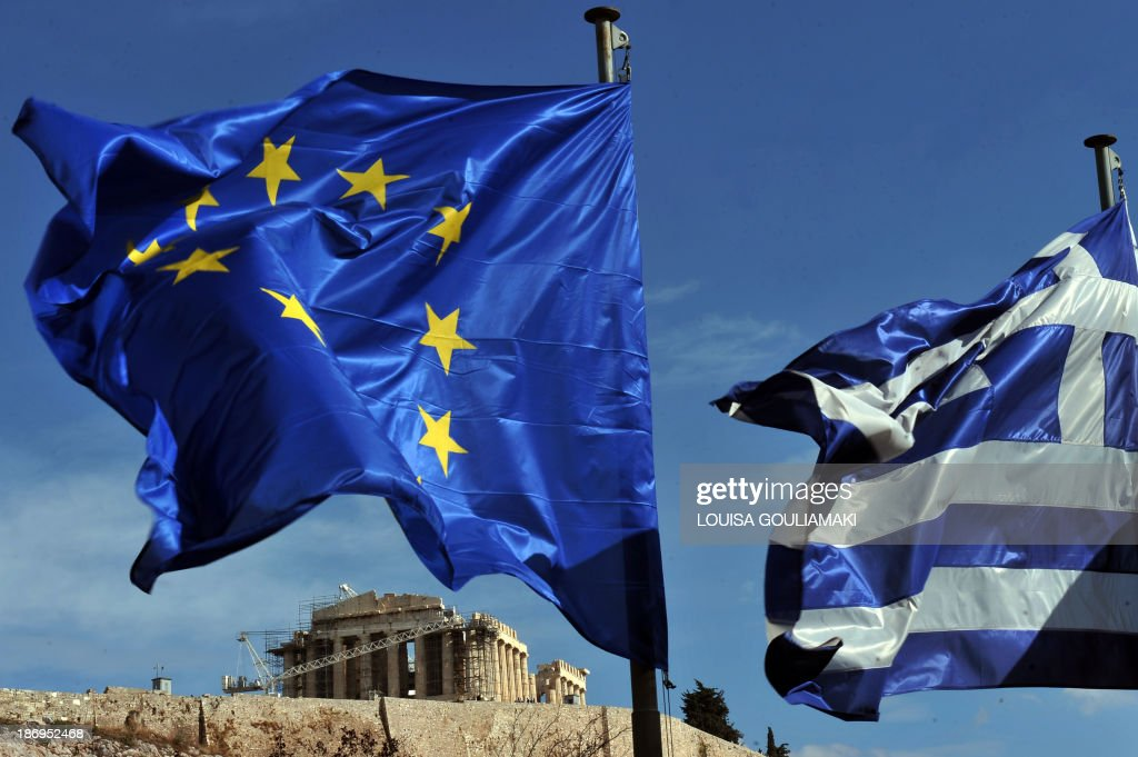 Greek and European union flags flutters in front of the Acropolis in Athens on November 5, 2013. The so-called troika of international creditors returned to Athens on November 4 for another round of crucial talks with Greece's debt-wracked government, as unions prepared for a general strike.