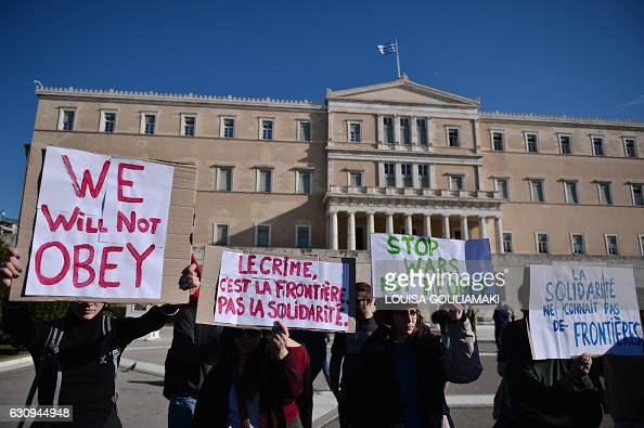 Greek and foreign promigrant activists hold placards reading 'Crime is the border not solidarity' and 'Solidarity knows no borders' as they...