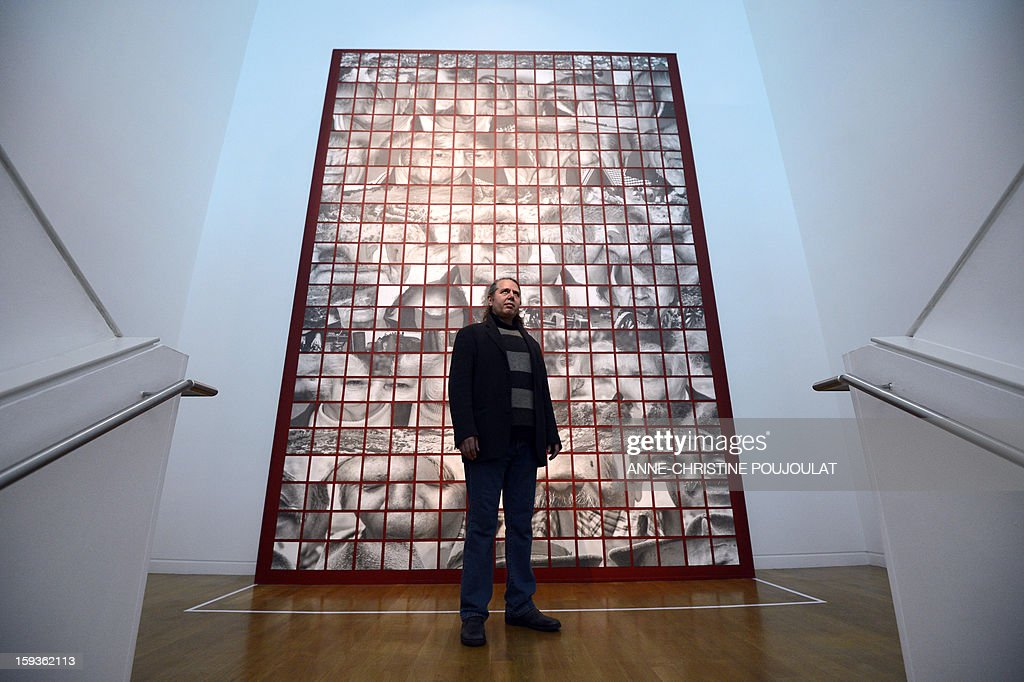 Greek artist Ilias Poulos poses in front of his work 'Memosis', displayed at the Granet museum on January 11, 2013, in Aix-en-Provence, at the 'Exquisite corpse, mediterranean suite' exhibition, one of the events marking the beginning and launch of festivities for the Marseille-Provence 2013 European Capital of Culture. AFP PHOTO / ANNE-CHRISTINE POUJOULAT CAPTION