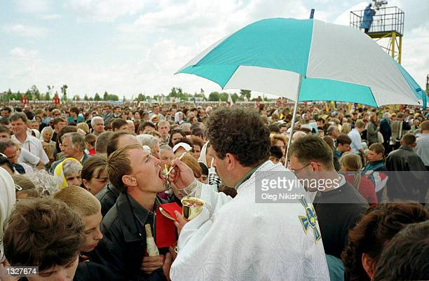 Greek Catholic priest gives communion to Ukrainian worshipers June 27 2001 during a liturgy celebrated by Pope John Paul II in the western Ukrainian...