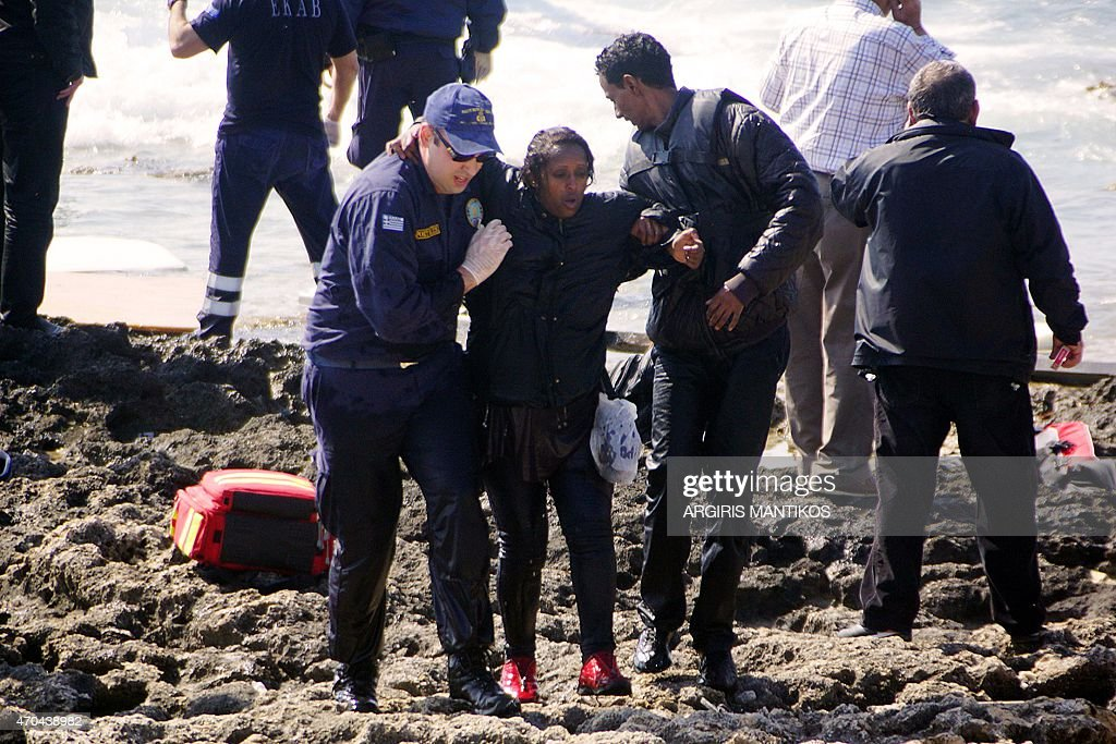 Greek coast guards help a migrant woman rescued after a boat carrying migrants sank off the island of Rhodes southeastern Greece on April 20 2015 At...
