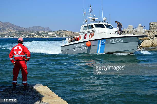 A Greek coastguard boat with migrants on board arrives at the port of Ierapetra on the Greek island of Crete on July 9 2013 The Greek coastguard...