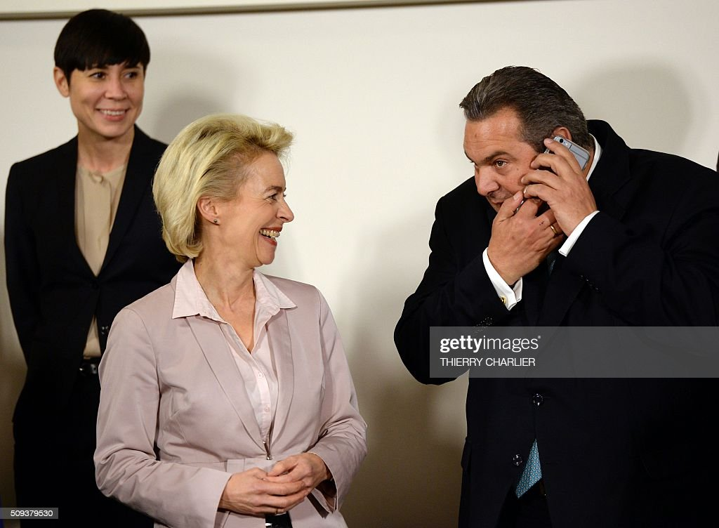Greek Defence Minister Panos Kammenos (R) uses his mobile phone while German Defence Minister Ursula von der Leyen (C) and Norwegian Defence Minister Ine Marie Eriksen Soreide (L) look on during a family photo following the North Atlantic Council (NAC) of Defence Ministers at NATO headquarter in Brussels on February 10, 2016. NATO defence ministers convene a two-day meeting to discuss current defense issues and whether the Alliance should take a more direct role in dealing with its gravest migrant crisis since Worl War II. / AFP / THIERRY CHARLIER