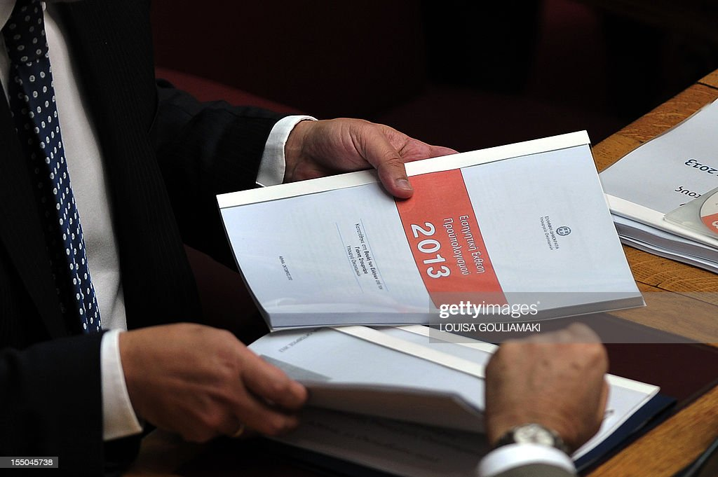 Greek deputy Finance Minister Yiannis Staikouras holds a document on the 2013 budget during a presentation of a draft budget to parliament outlining new austerity measures needed to unlock fresh rescue loans on October 31, 2012 in Athens. Greece revised downwards its recovery forecasts in a 2013 budget that predicted an economic contraction of 4.5 percent of output and a public deficit of 5.2 percent.