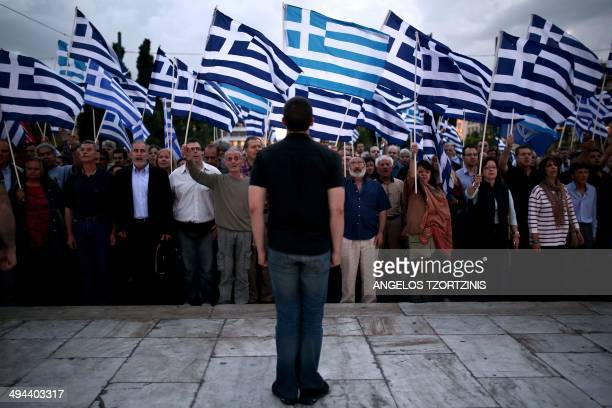 Greek far right party Golden Dawn's spokesman Ilias Kasidiaris and supporters of the party chant the national anthem in front of the Greek parliament...