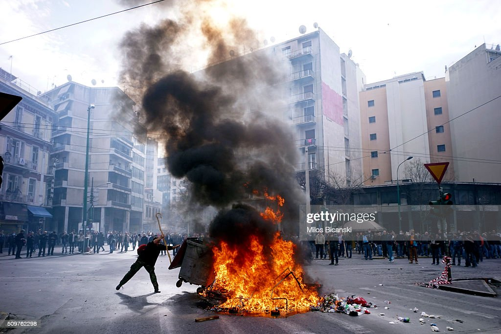 Greek farmers burn a garbage container during a protest against planned pension reforms outside the Agriculture ministry on February 12, 2016 in Athens, Greece. Around reportedly 800 protesters from Crete gathered outnumbering police who were armed with teargas.
