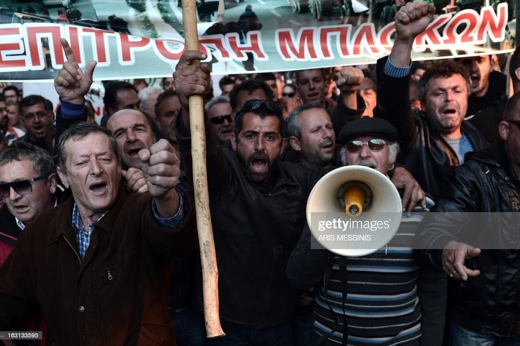 Greek farmers shout slogans during a demonstration in central Athens on March 5, 2013. Over 2,000 Greek farmers gathered in Athens to demand lower taxes, arguing that the rising cost of fuel and electricity was driving them to ruin.The farmers also called for subsidies from the heavily indebted state, which has been forced to undertake a tough austerity policy, to help them lower their costs and remain competitive. AFP PHOTO / ARIS MESSINIS
