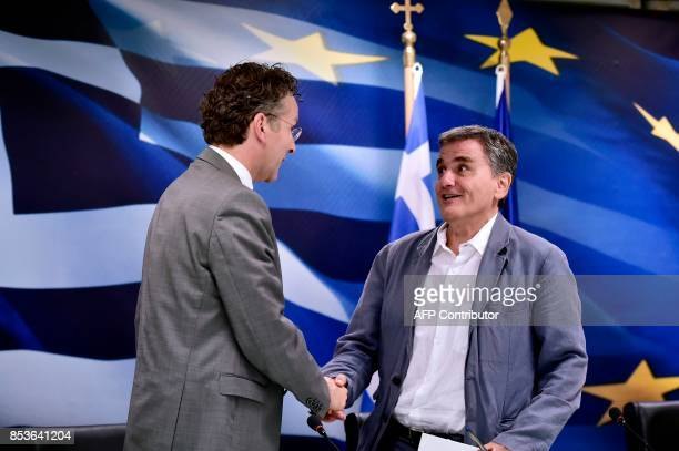 Greek Finance Minister Euclid Tsakalotos greets the Chair of the Eurogroup finance ministers Jeroen Dijsselbloem during their joint press conference...