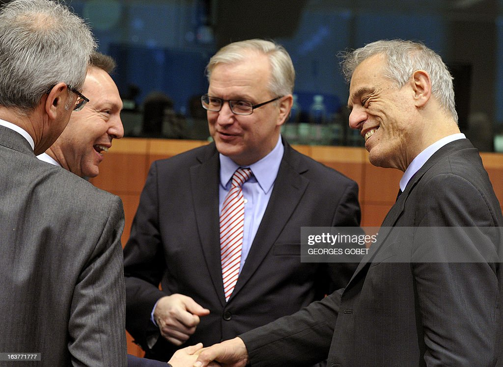 Greek Finance Minister Ioannis Stournaras, EU Commissioner for Economic and Monetary Affairs Olli Rehn and Cypriot Finance Minister Michael Sarris talk prior to a Eurozone meeting on March 15, 2013 at the EU Headquarters in Brussels. Finance ministers of the euro zone were expected late on March 15 afternoon to try to complete the plan of aid to Cyprus, wishing to obtain the eurozone and the IMF loan of 17 billion euros the equivalent of the gross domestic product.
