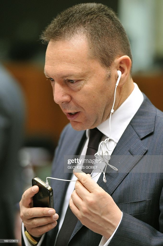 Greek Finance Minister Ioannis Stournaras uses earphones to talk on his smartphone upon his arrival at an Economic and Financial Affairs Council on March 5, 2013 at the EU Headquarters in Brussels. The Council will take note of progress on a draft directive on bank recovery and resolution, a proposal that is part of a broader plan to establish a banking union. It will also examine a package of measures aimed at combating VAT fraud – the 'quick reaction mechanism' and the 'reverse charge mechanism' – and will be called on to adopt conclusions.