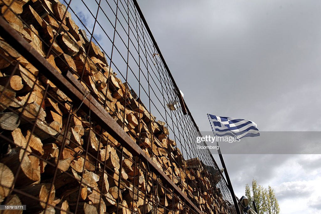 A Greek flag flies from a flagpole near drying firewood outside a wood supply store in Athens, Greece, on Friday, Dec. 7, 2012. Greece, the epicenter of Europe's debt crisis since revealing a bloated spending gap in late 2009, has faced regular demands to get a firmer grip on the budget or risk being forced out of the euro. Photographer: Kostas Tsironis/Bloomberg via Getty Images