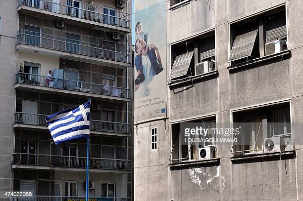 A Greek flag is pictured in front of the Ministry of Health in Athens on May 20 2015 Health sector workers staged a 24hours strike to demand funds...