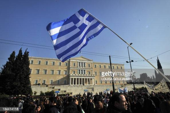 A Greek flag is waved in front of the Greek Parliament while strikers march by during a protest march in Athens marking the 24hours general strike on...