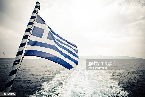 Greek flag sailing away from the mainland