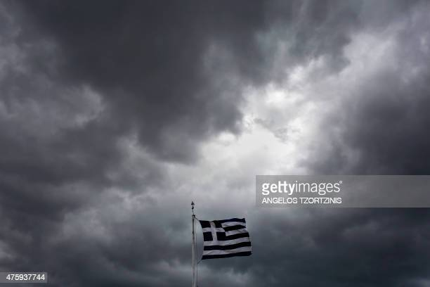 A Greek flag waves in the breeze at Acropolis hill in Athens on June 5 2015 Greece bought time in debt crisis negotiations with official creditors...