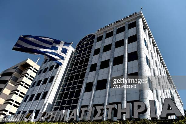 A Greek flag waves outside the Athens Stock Exchange on August 3 2015 Greece's stock exchange reopened with a drop of more than 22 percent after a...