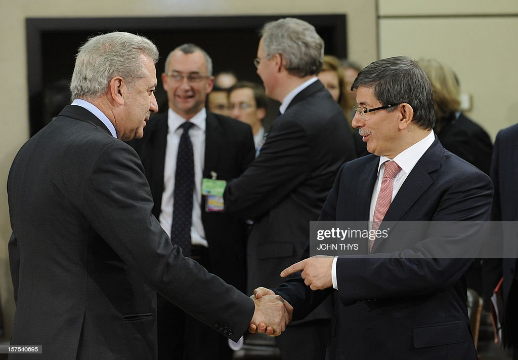 Greek Foreign Minister Dimitrios Avramopoulos (L) shakes hands with his Turkish counterpart Ahmet Davutoglu on December 4, 2012 at North Atlantic Treaty Organization (NATO) headquarters in Brussels during a meeting of foreign ministers from the 28 NATO member-countries to discuss Syria and Turkey's request for Patriot missiles to be deployed protectively on the Turkish-Syrian border. AFP PHOTO / JOHN THYS