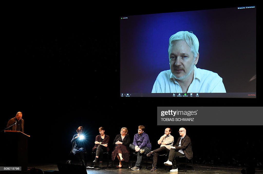Greek former Finance Minister Yanis Varoufakis and other politicians listen to WikiLeaks founder Julian Assange speaking on a screen during an event to mark the official launch of the Democracy in Europe Movement (DiEM) in Berlin on February 9, 2016. / AFP / TOBIAS SCHWARZ