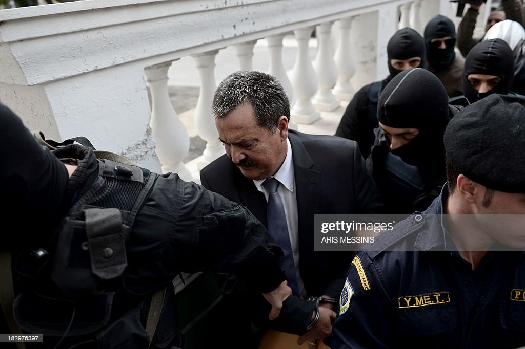 Greek Golden Dawn lawmaker Christos Pappas is ecorted to a court in Athens on October 3, 2013. The leader of Greece's Golden Dawn party, Nikos Michaloliakos, was to be taken to a high-security prison following his indictment on criminal charges as the government cracks down on the neo-Nazi group. Four Golden Dawn lawmakers were also charged with membership of a criminal group and the party's deputy leader Pappas appeared in court on the same charges.