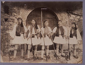 Greek guards pose in front of a portal They dress in a uniform of white linen and green woolen cloth with green embroidery with a red felt fez with...