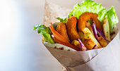 greek gyros with fried squid rings breaded, tzatziki sauce, vegetables, feta cheese and french fries