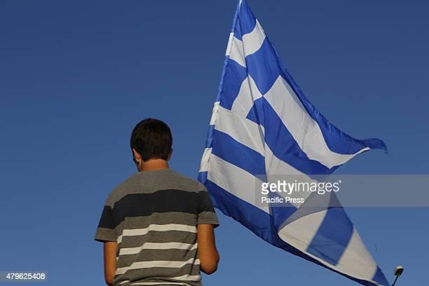 Greek holds a Greek flag Greek participated in the votation of referendum