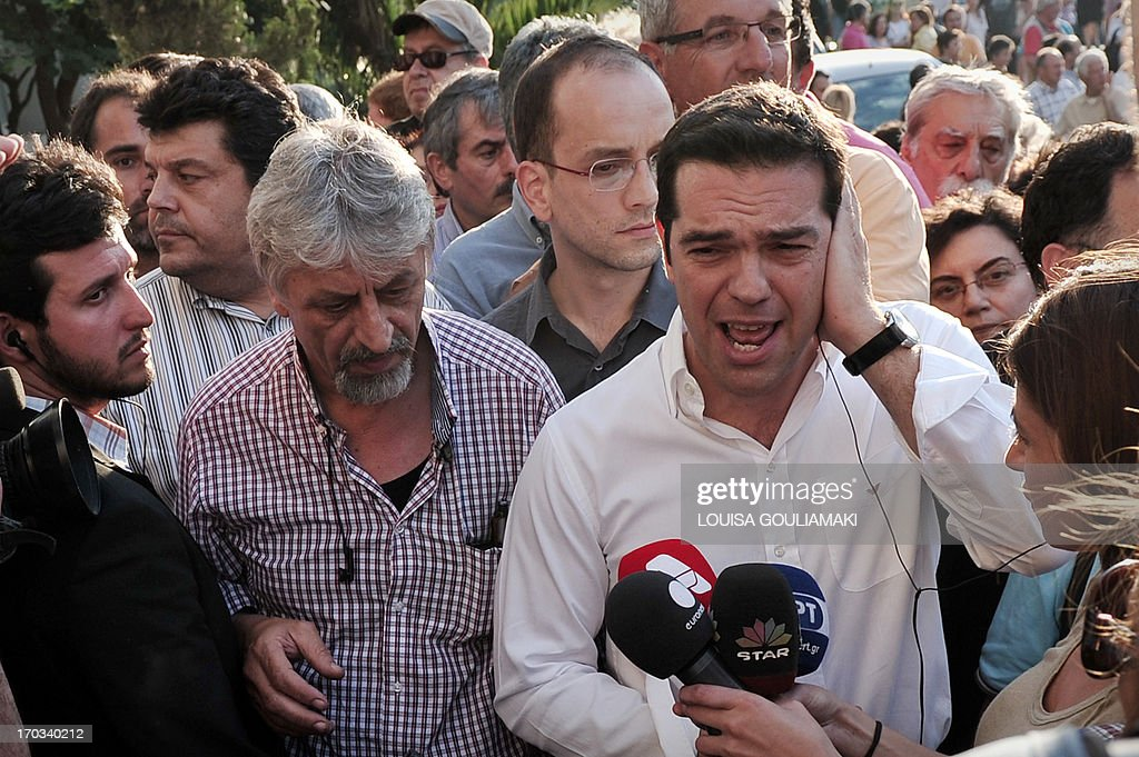 Greek main opposition Syriza party leader Alexis Tsipras (R), who rushed to the ERT premises, talks to reporters on June 11, 2013, while thousands of demonstrators gather outside the Greek public television and radio broadcaster ERT headquarters in Athens northern suburb, after Greece's government announced on June 11, 2013 the immediate closure of ERT in a move that reportedly affects about 2,700 jobs. AFP PHOTO/ LOUISA GOULIAMAKI