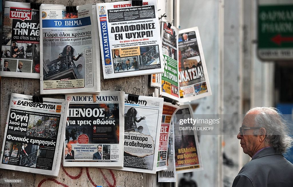 A Greek man checks newspapers in the center of Athens on May 6, 2010. A fire-bomb attack on a bank in Greece killed at least three people on May 5, as police fought pitched battles with striking protestors furious at brutal budget cuts designed to avert national bankruptcy. Greek unions mobilised Thursday for new demonstrations against draconian austerity cuts as the government raced to push the unprecedented measures through parliament a day after deadly rioting.