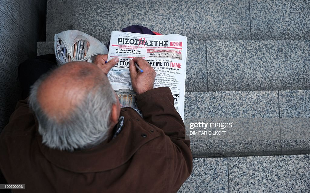 A Greek man reads a newspaper in the center of Athens on May 5, 2010. A nationwide general strike gripped Greece in the first major test of the socialist government's resolve to push through unprecedented austerity cuts needed to avert fiscal meltdown.