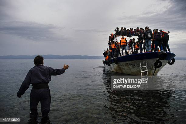 A Greek man talks to migrants arriving by boat on the Greek island of Lesbos after crossing the Aegean sea from Turkey on October 11 2015 Greece was...