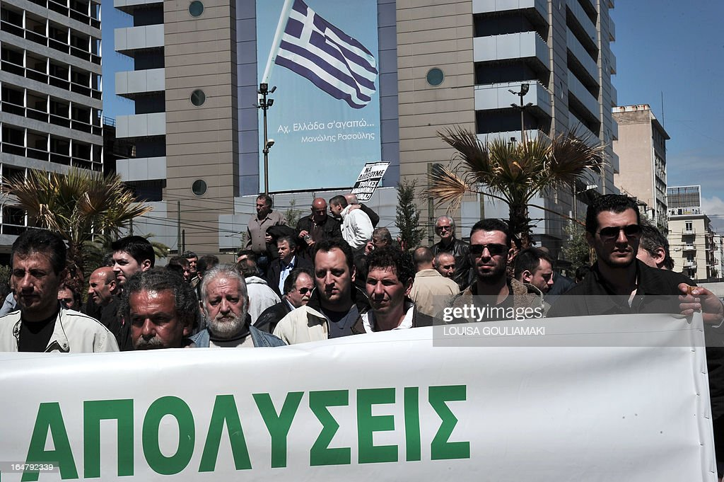 Greek metal workers hold a banner reading 'lay-offs' as they march towards the Finance ministry in Athens on March 28, 2013 to protest the government's austerity measures and high unemployment in their sector. AFP PHOTO / LOUISA GOULIAMAKI