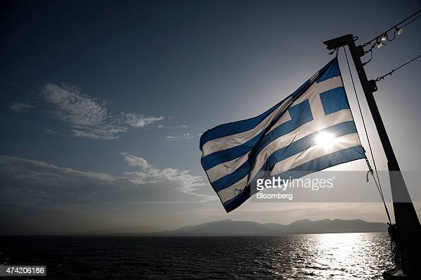 A Greek national flag flies aboard a passenger ferry as it departs to the Aegean islands from the port of Piraeus Greece on Wednesday May 20 2015 The...