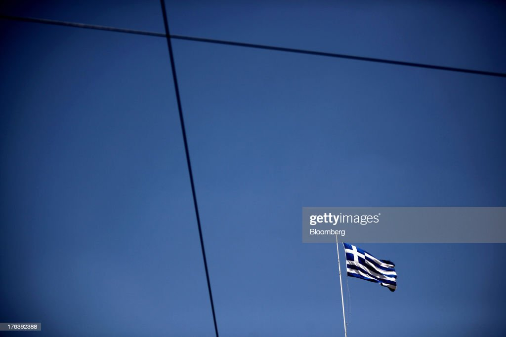 A Greek national flag flies above a building in Athens, Greece, on Saturday, Aug. 10, 2013. Greece's economy contracted for a 20th quarter, extending an economic slump that has left more than six in 10 young Greeks out of work. Photographer: Angelos Tzortzinis/Bloomberg via Getty Images