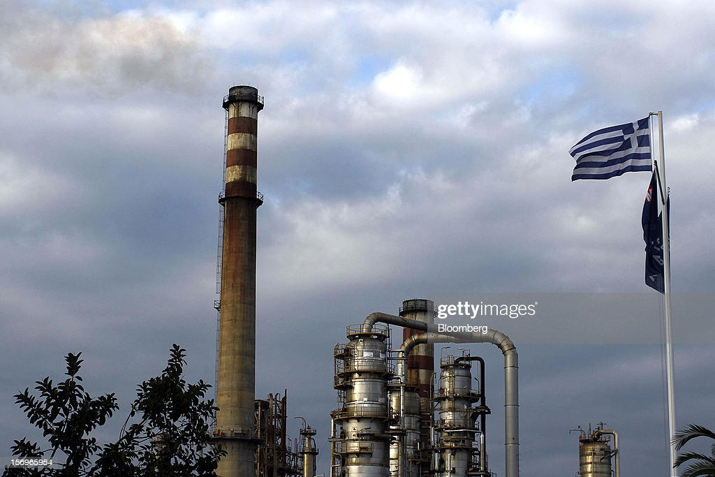 A Greek national flag flies from a flagpole near refining towers at the Motor Oil Hellas SA oil refinery in Agioi Theodoroi, Greece, on Friday, Nov. 23, 2012. Motor Oil Hellas SA Chief Financial Officer Petros Tzanetakis said Greek companies face difficulties in securing financing as foreign banks look at Greece with a 'skeptical eye.' Photographer: Kostas Tsironis/Bloomberg via Getty Images
