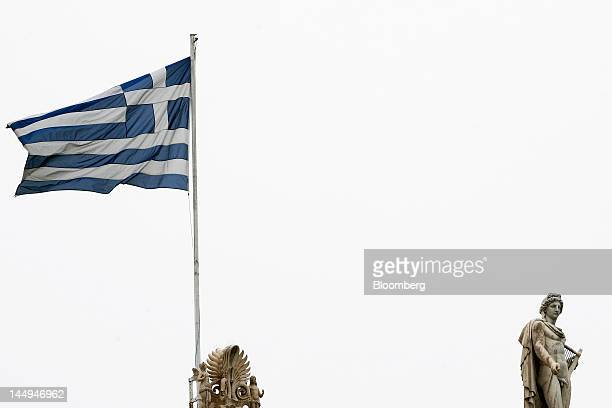 A Greek national flag flies from the roof of Athens University near a sculpture of the Greek god Apollo in Athens Greece on Monday May 21 2012...