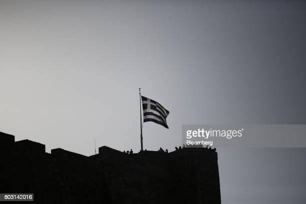A Greek national flag flies from the top of the Acropolis hill above visiting tourists in Athens Greece on Wednesday June 28 2017 The change in...