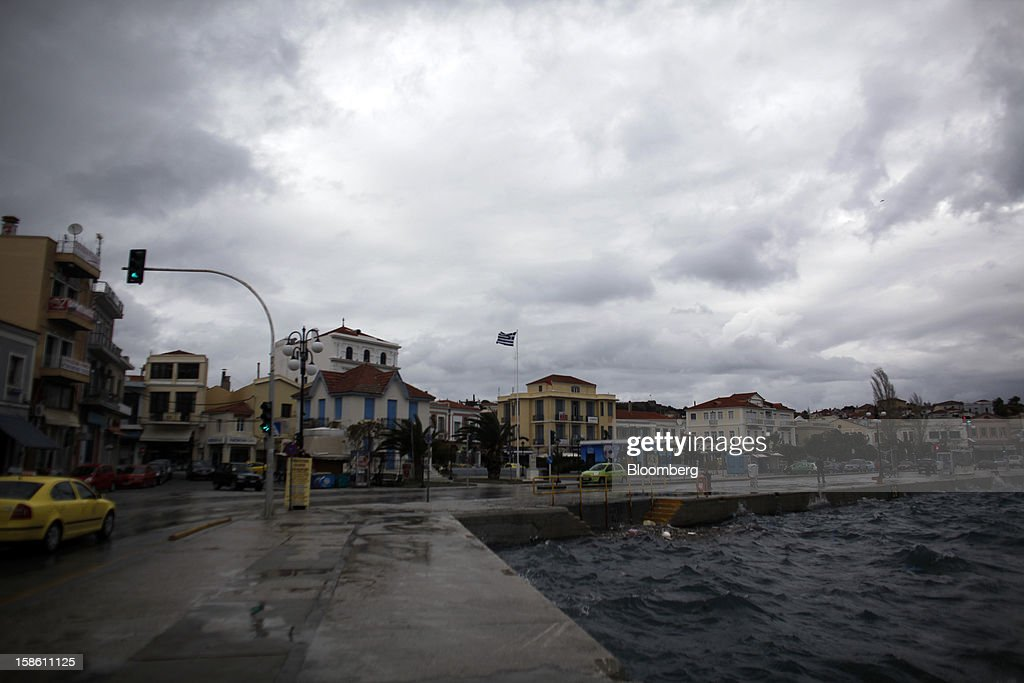 A Greek national flag flies in strong wind on the harbor front in the town of Mytilene on the island of Lesbos, Greece, on Sunday, Dec. 9, 2012. In recent months, Lesbos has become a hot spot for migrants as Greece struggles to cope with waves of refugees from Middle Eastern conflict even as it reels from economic crisis at home. Photographer: Kostas Tsironis/Bloomberg via Getty Images