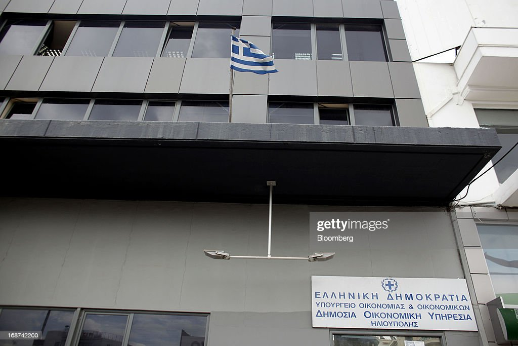A Greek national flag flies outside a tax office in the Ilioupolis district of Athens, Greece, on Tuesday, May 14, 2013. Greek Prime Minister Antonis Samaras said the country can beat the targets set under its 240 billion-euro ($311 billion) International Monetary Fund and euro area bailout program and return to bond markets in the first half of next year. Photographer: Kostas Tsironis/Bloomberg via Getty Images