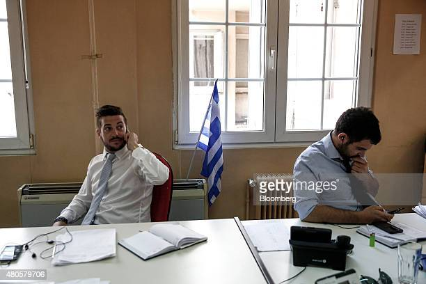 A Greek national flag hangs on a wall behind traders working inside the offices of Nuntius Securities SA brokers in Athens Greece on Monday July 13...