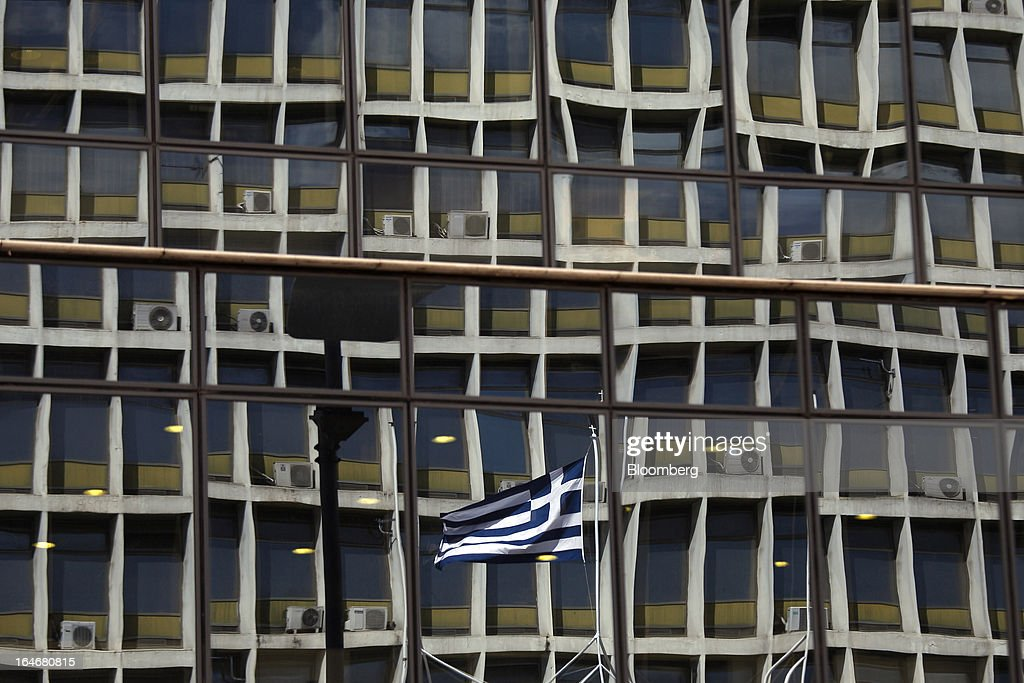 A Greek national flag is reflected in office windows above a closed Kyprou Leasing branch, which is a member of the Bank of Cyprus Plc group, in Athens, Greece, on Tuesday, March 26, 2013. Piraeus Bank SA acquires Greek units of Cypriot lenders for total cash consideration of EU524m, according to e-mailed statement from the Athens-based lender today. Photographer: Kostas Tsironis/Bloomberg via Getty Images
