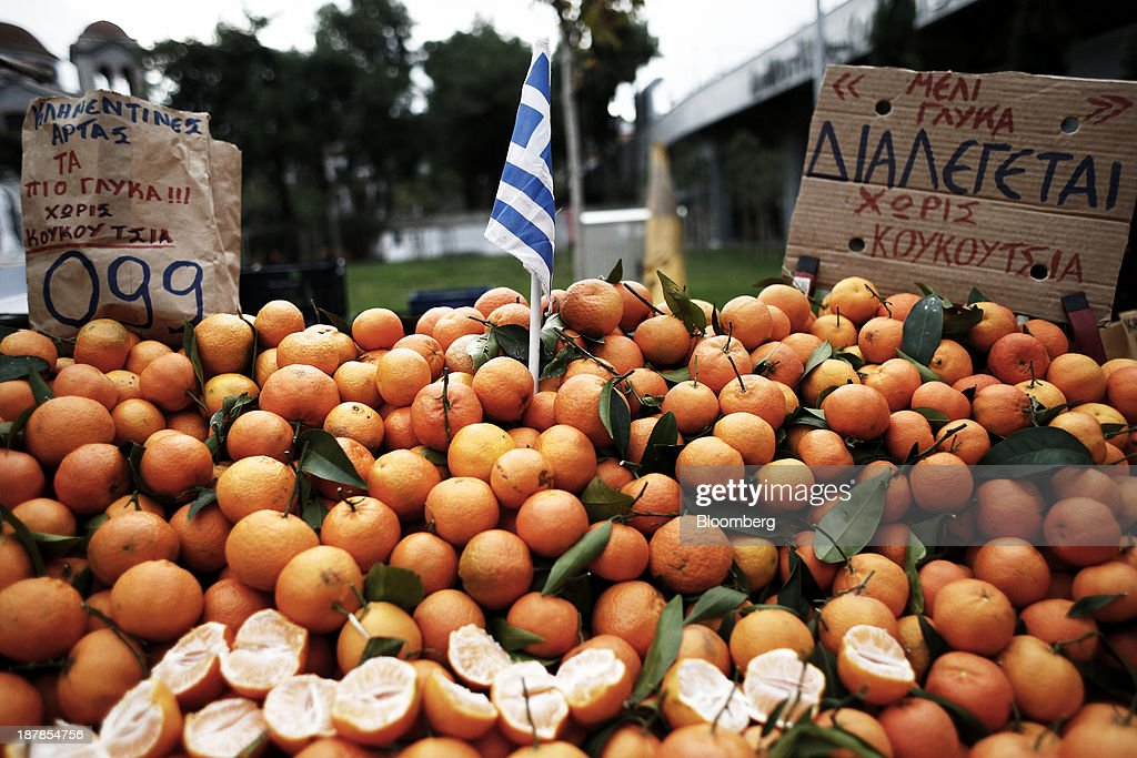 A Greek national flag stands in a display of mandarin oranges for sale at a farmer's market in the Toumpa district of Thessaloniki, Greece, on Wednesday, Nov. 13, 2013. Greece 'is following a fiscal adjustment program that aims to make the country's public finances sustainable on a permanent basis,' Finance Minister Yannis Stournaras told lawmakers during the debate, after holding talks with the troika earlier in the week. Photographer: Konstantinos Tsakalidis/Bloomberg via Getty Images