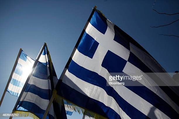 Greek national flags fly above a street vendor's stall at Syntagma square in Athens Greece on Friday Feb 20 2015 Germany and its allies turned up the...