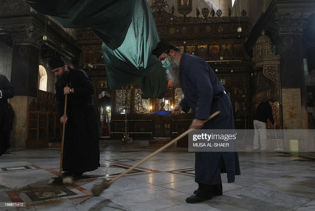 Greek Orthodox and Armenian clergy clean the Church of Nativity on January 2, 2013, in the West Bank town of Bethlehem. The sovereignty of the Church of the Nativity, traditionally believed to be the birthplace of Jesus Christ, is shared by the Christian denominations, who also share the annual cleaning responsibilities.
