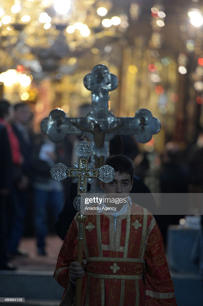 A Greek Orthodox boy carries a cross during the Christmas mas at Nativity Church in Bethlehem, West Bank on January 6, 2014.
