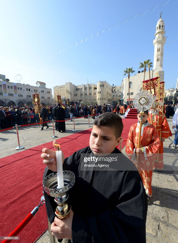 A Greek Orthodox boy holds a candle during the ceremony of Christmasat Nativity Church in Bethlehem, West Bank on January 6, 2014.