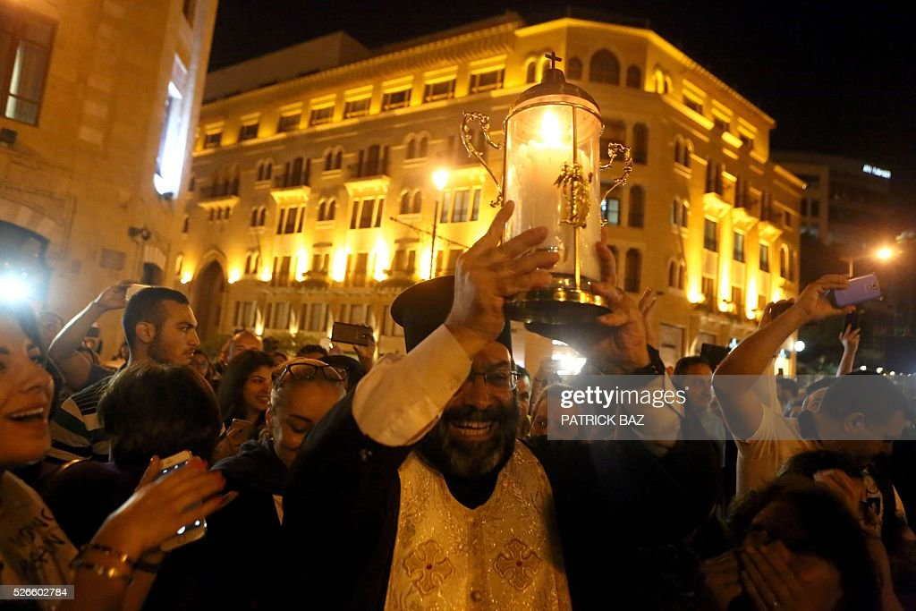 A Greek Orthodox Christian priest holds the Holy Fire as he arrives in downtown Beirut from Jerusalem through Amman on April 30, 2016. The Holy Fire is described by Orthodox Christians as a miracle that occurs every year at the Church of the Holy Sepulchre in Jerusalem on Great Saturday, or Holy Saturday, the day preceding Orthodox Easter. / AFP / PATRICK BAZ