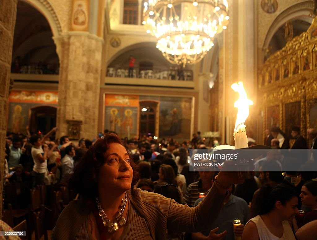 A Greek Orthodox Christian woman holds the Holy Fire, which was brought from Jerusalem through Amman, at the Saint George church in the Lebanese capital Beirut, on April 30, 2016. The Holy Fire is described by Orthodox Christians as a miracle that occurs every year at the Church of the Holy Sepulchre in Jerusalem on Great Saturday, or Holy Saturday, the day preceding Orthodox Easter. / AFP / PATRICK BAZ