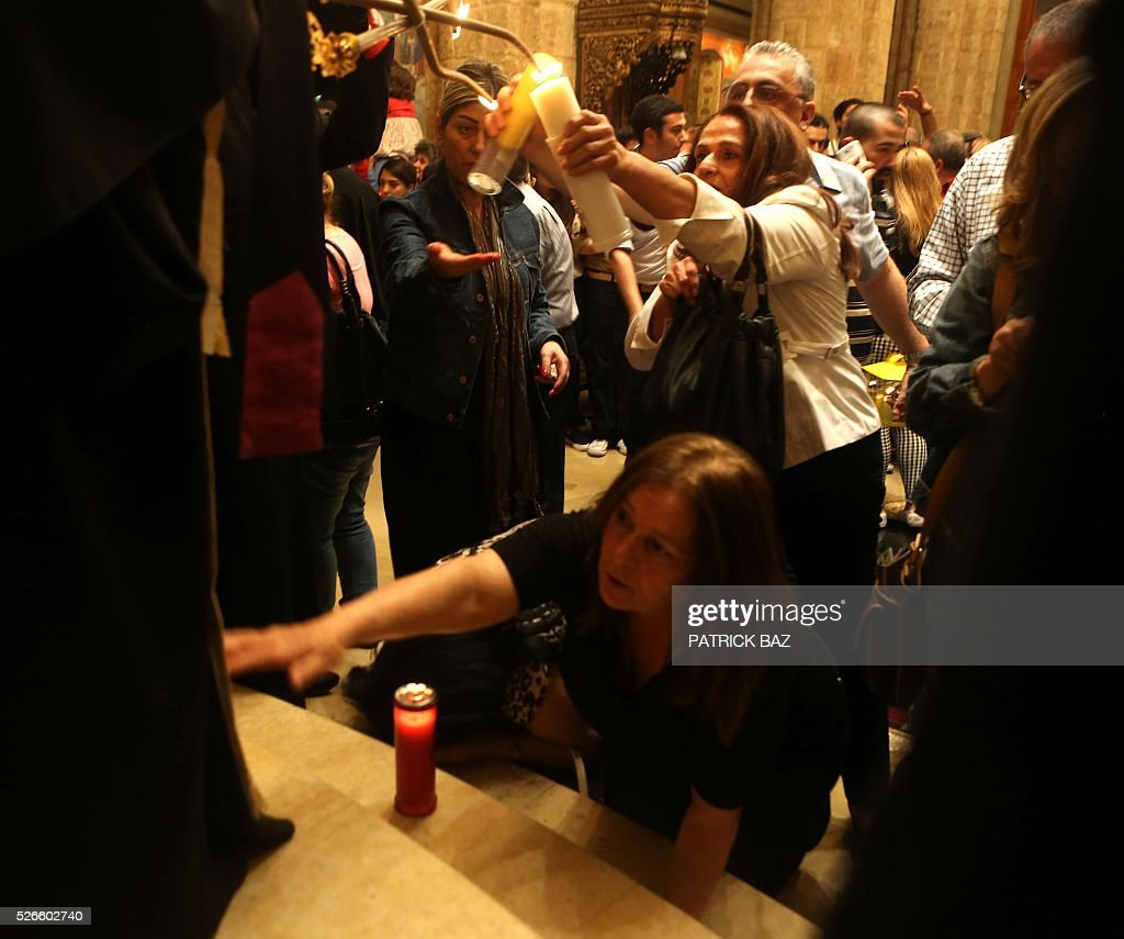 A Greek Orthodox Christian woman touches the robe of her Patriarch while others share the Holy Fire, which was brought from Jerusalem to Beirut through Amman, at the Saint George church in downtown Beirut, on April 30, 2016. The Holy Fire is described by Orthodox Christians as a miracle that occurs every year at the Church of the Holy Sepulchre in Jerusalem on Great Saturday, or Holy Saturday, the day preceding Orthodox Easter. / AFP / PATRICK BAZ