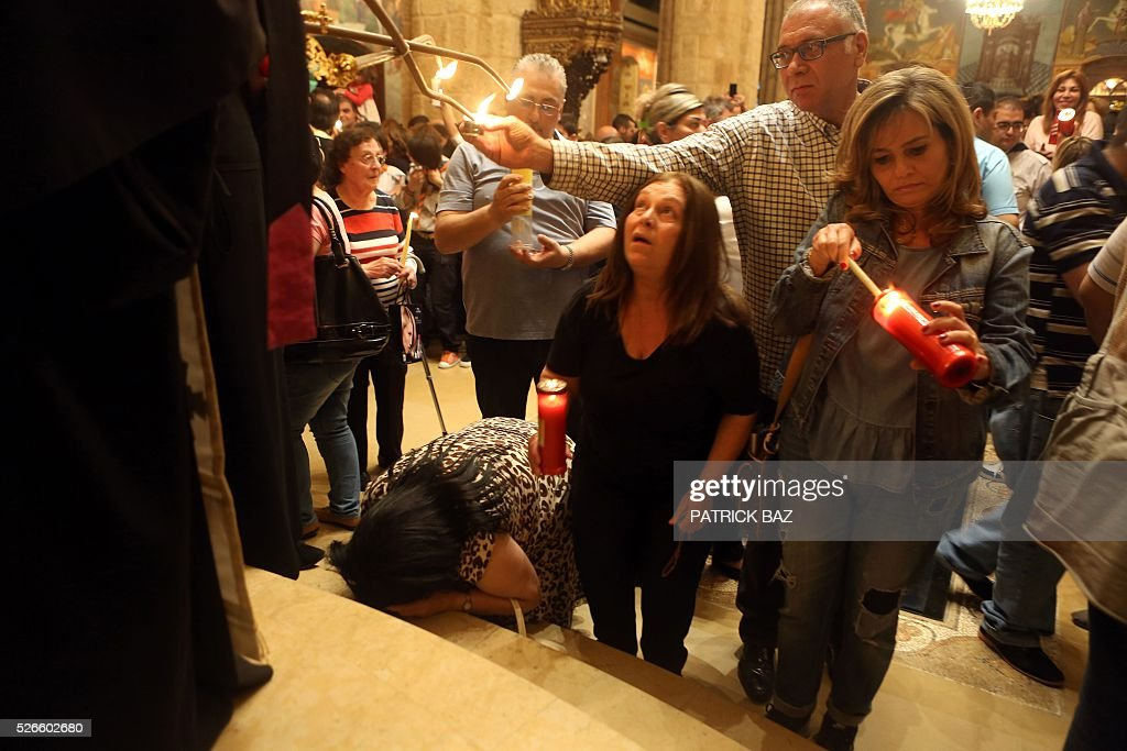 Greek Orthodox Christians kneel and light candles in front of their Patriarch while others share the Holy Fire, that was brought from Jerusalem through Amman, at the Saint George church in downtown Beirut, on April 30, 2016. The Holy Fire is described by Orthodox Christians as a miracle that occurs every year at the Church of the Holy Sepulchre in Jerusalem on Great Saturday, or Holy Saturday, the day preceding Orthodox Easter. / AFP / PATRICK BAZ